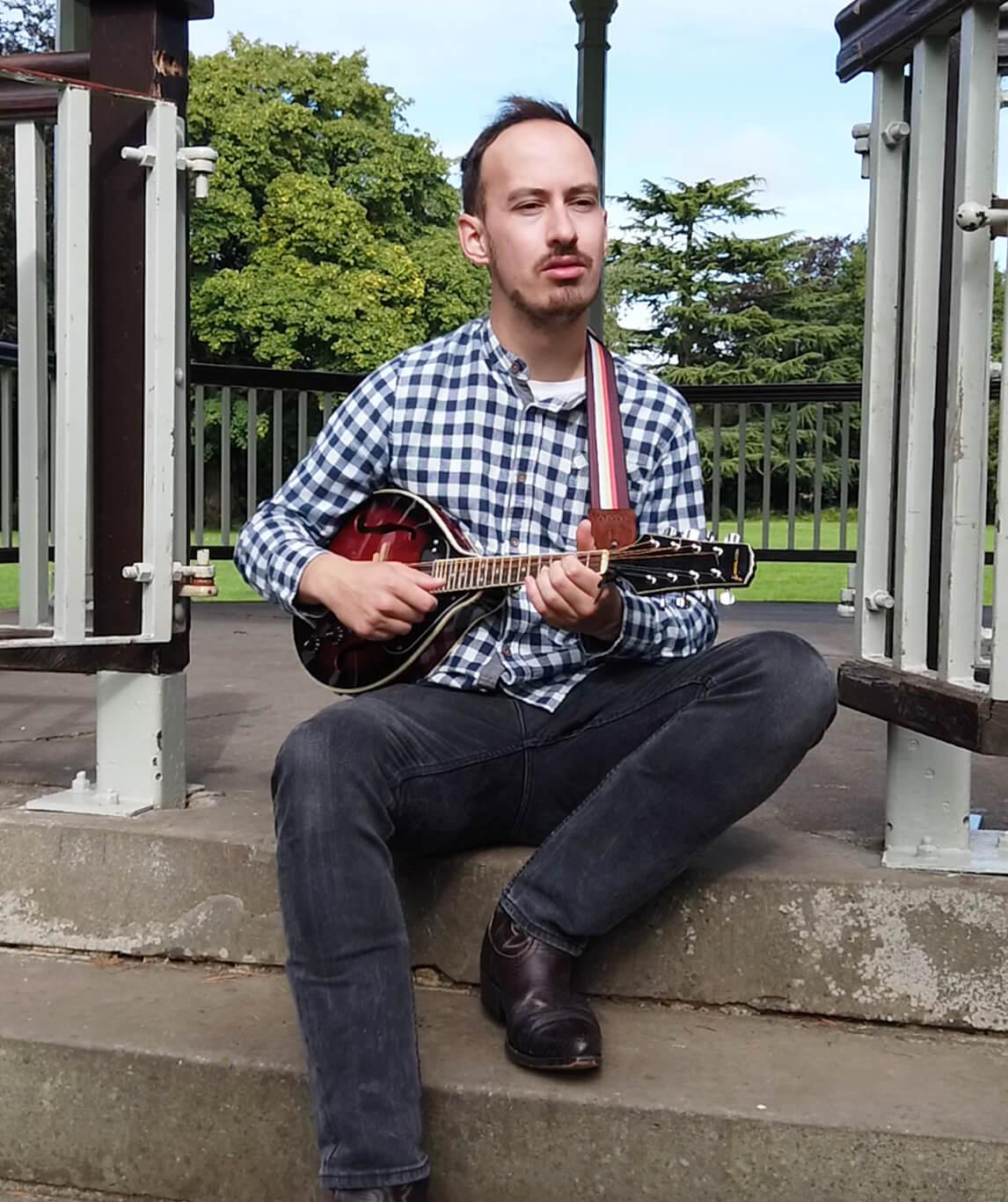 Ben Atkinson sitting on some steps and playing a Mandolin