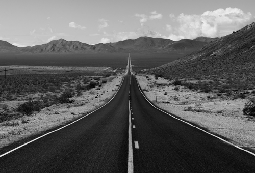 A long tarmac road in the middle of the desert, part of the cover art for Ben's album Cold Hard Shoulder.